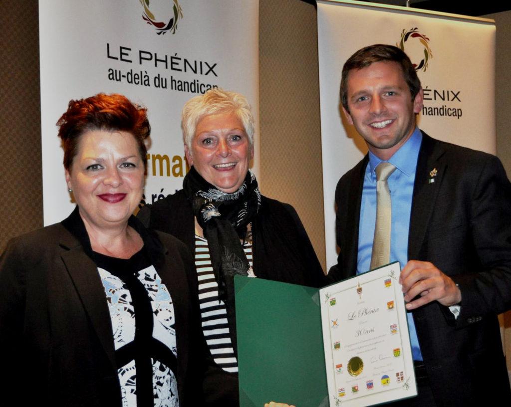 Présentation par le député fédéral de Glengarry-Prescott-Russell, Francis Drouin, à la présidente Natalie Béland (g.) et à la directrice générale, Judith Parisien (c.).